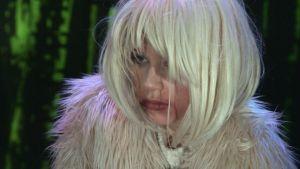 En kvinna från filmen Dream Business i peruk.