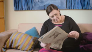 Anni bläddrar i gammal tidning