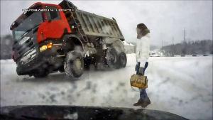 Nainen katsoo lumessa kallellaan olevaa kuorma-autoa