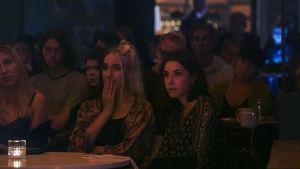 Unga personer sitter och lyssnar på spelning i mörkt kaféutrymme.