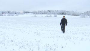 En man går på en snöig åker.