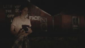 Lyhytelokuvan päähenkilö pimeässä illassa graffitilla sotketun talon edessä