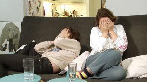 Salli ja Teemu istuvat sohvalla ja peittävät silmänsä.