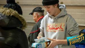 Nuori mies maitpurkki ja levitepaketti kädessä.