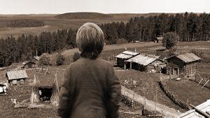 Kuvituskuva kuunnelmaan Mahtimiehen poika. Pojan selkä ja keskiaikainen kylä.