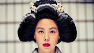 Nuori perinteiseen asuun pukeutunut nainen lähikuvassa. Kuva korealaisesta elokuvasta Handmaiden.