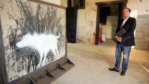 Taidekauppias esittelee katutaiteilija Banksyn koiramaalausta, joka on leikattu irti Palestiinan muurista
