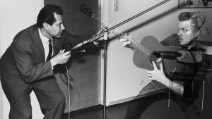 Editoidussa kuvassa toimittaja Martti Silvennoinen, joka tutustuu ääntä kaukaa ottavaan orumikrofoniin v.1957 ja häntä vastapäätä on kitaraa soittava mies osin pikselöitynä v.2019