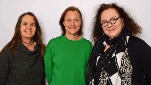 Kolme naista hymyilee.