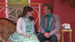 Två personer på en teaterscen iklädda scenkläder.