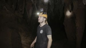 Sukeltaja Mikko Paasi seisoo pimeässä luolassa taskulampun kanssa.