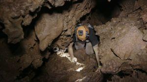 Mikko Paasi ryömii ahtaassa luolastossa.