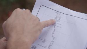 Mikon sormet näyttävät luolaston muotoja kartalta.