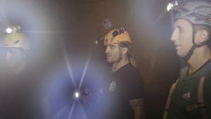 Mikko kosteassa luolassa kahden miehen kanssa.