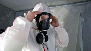 Rakennustyömies pukee suojapuvun ja hengityssuojaimen asbestityömaalla.