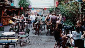 Ihmisiä istumassa sisäpihalla olevassa baarissa.