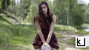 Kirjailija Siiri Enoranta istuu tukin päällä ja katsoo kameraan.