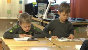 Två pojkar sitter vid en pulpet och läser böcker.