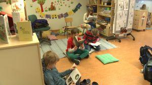Flera barn sitter i ett klassrum och läser böcker.