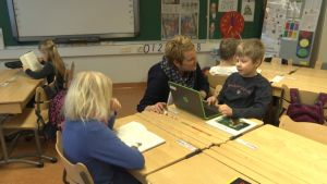 Lärare jobbar tillsammans med en elev i ett klassrum.