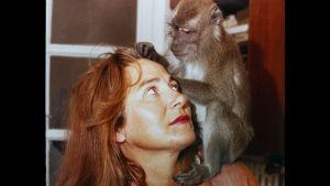 Nainen olkapäällään apina.