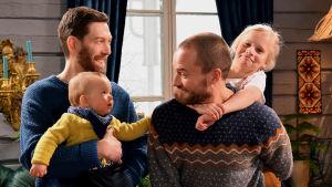 Kaksi hymyilevää miestä joilla on lapsi joko sylissä tai selällä.