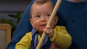 Vauva leikkii puukepillä.