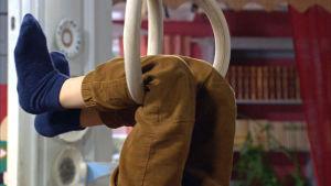 Ett barns ben hänger i ringar.