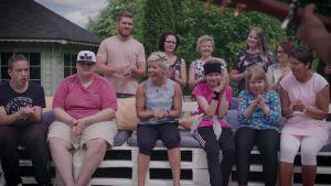Lastenkoti Jelperin nuoret ja ohjaajat istuvat yhdessä katsomassa Mikko Harjun SuomiLOVE-esitystä.