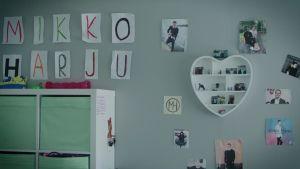 Seinä, jossa on useita leikekuvia Mikko Harjusta, sekä Mikko Harju -teksti kirjoitettuna piirrustuspaperille niin, että yhdellä paperilla on yksi kirjain artistin nimestä.