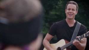Mikko Harju soittaa kitaraa ja laulaa kesäisessä maisemassa Jennulle. Tytön hahmo näkyy epätarkkana kuvan etuosassa.