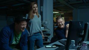 Kolme hakkeria iloitsee tietokoneen ääressä.