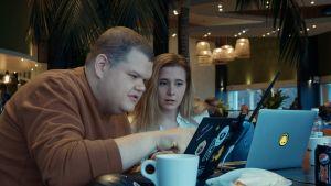 Iiro Uusitalo ja Laura Kankaala tietokoneen kanssa kahvilassa.