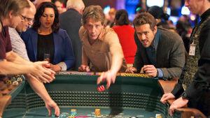 Ihmisiä heittämässä noppia oletettavasti jossakin kasinolla. Kuvassa mm. Ryan Reynolds.