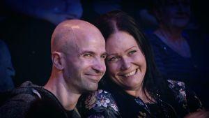 Umpirakastunut pariskunta hymyilee SuomiLOVEn yleisössä.