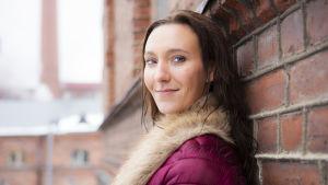 Saija Viherlaakso nojaa ulkona tiiliseinään, hymyilee.