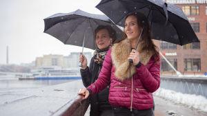 Pirjo ja Saija Viherlaakso seisovat ulkona räntäsateessa sateenvarjojen alla.