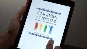 """Pärmen till Thomas Eriksons bok """"Omgiven av idioter"""""""