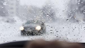 En bil i vinterlandskap syns genom en blöt vindruta.