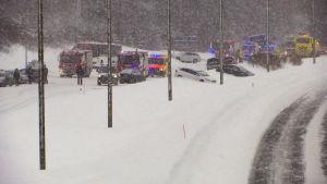 Utryckningsfordon och bilar som kört av vägen in i snödrivor.