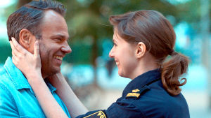 Polisen Ulrika lägger händerna kärleksfullt runt maken Roberst ansikte.