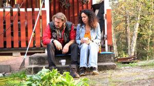 Anders och Nahid sitter på stugtrappa och ser ledsna ut.