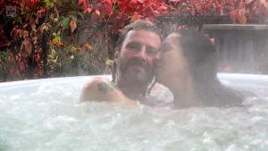 Nahid pussar Anders i ångande bubbelbad i trädgården.