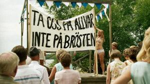 """Lottie (Maja Rung) ja banderolli mielenosoituksessa: """"Ta oss på allvar, inte på brösten"""""""