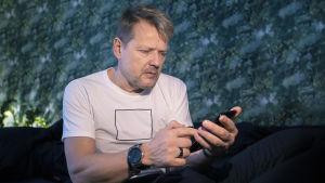 Risto Kuusisto istuu yöllä sängyssä, tuijottaa kännykkää.