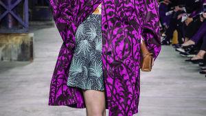 Yksityiskohta Dries Van Notenin suunnittelemasta asusta: musta-purppura takki ja musta-turkoosi hame