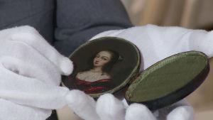 Kuvassa valkoisilla hansikkailla verhotut kädet pitävät medaljonkia.