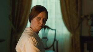 Nainen katsoo epäilevän näköisenä jonnekin verhoilla pimennetyssä huoneessa.