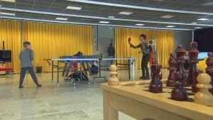 En kvinna och ett barn spelar pingis med ett schackbräde i förgrunden.