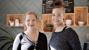 Två medelålders kvinnor i ett kafè ler och tittar in i kameran